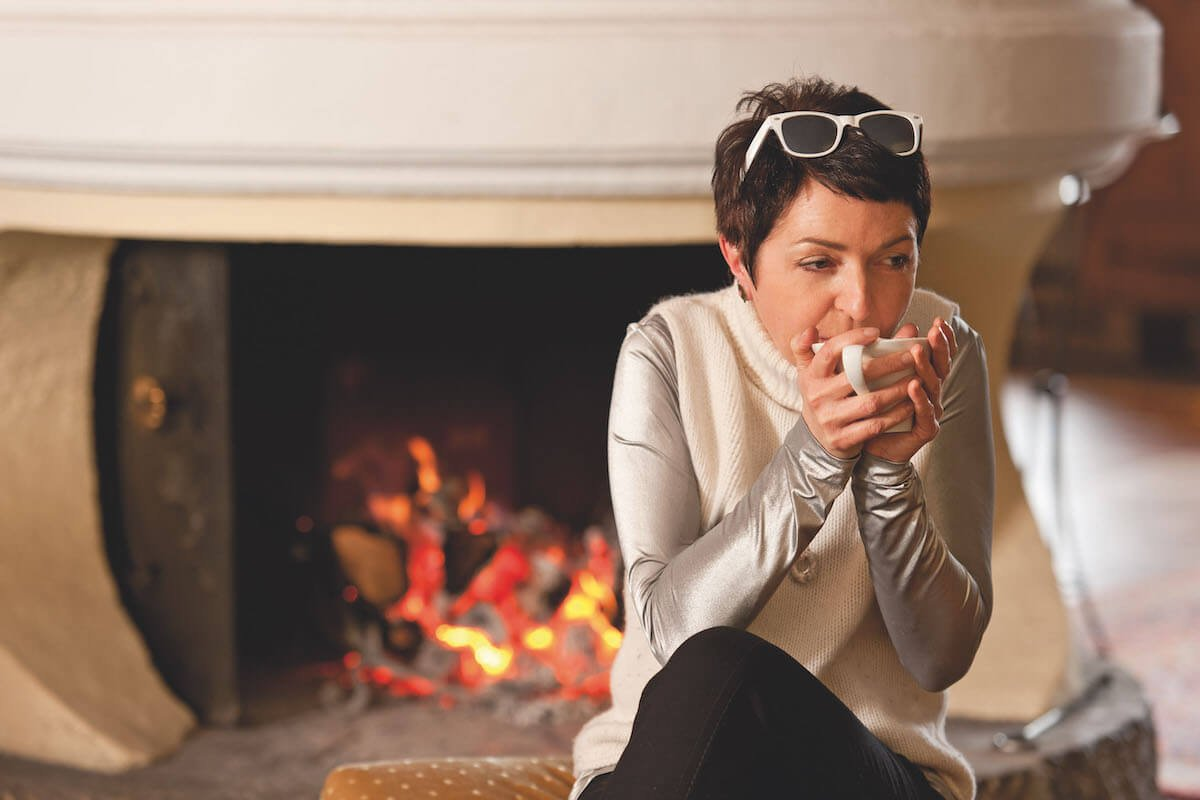 Woman in front of the fireplace with a hot tea.