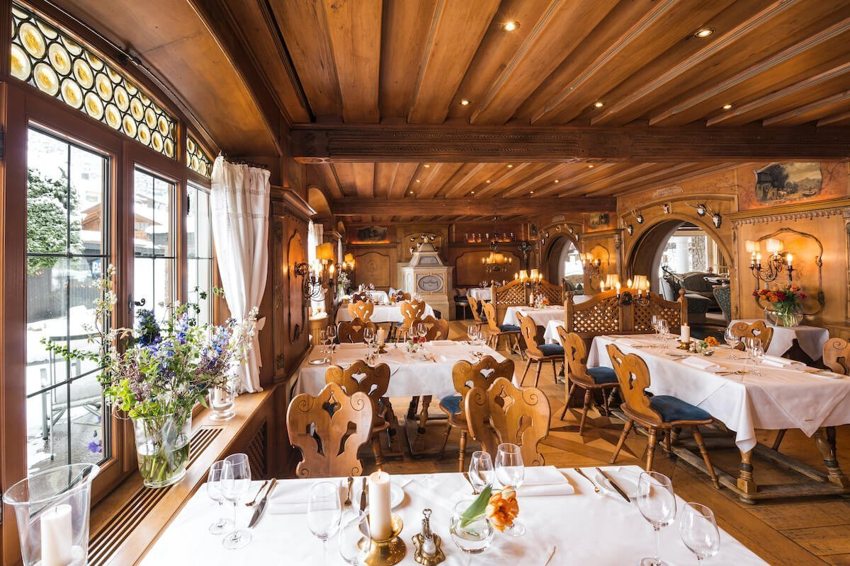 View into the restaurant Alte Stube. Elegant farmhouse parlor with wood panelling and poker painting.