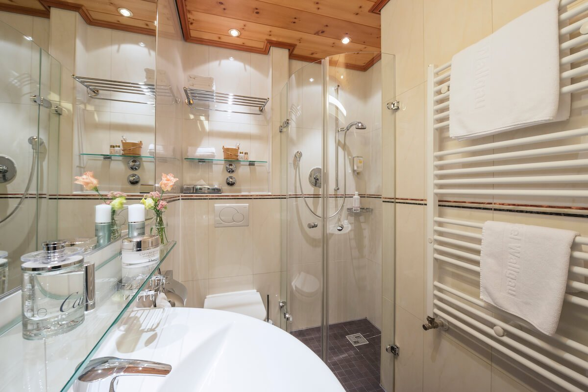 Small but nice are the modern bathrooms with round glass shower, wash basin, towel warmer and toilet. On the ceiling you will find the tasteful Swiss stone pine again