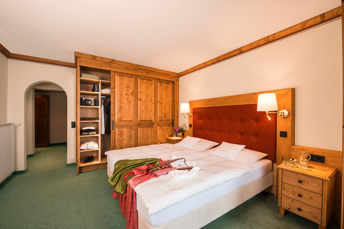 The village view room with double bed and illuminated closet in dark oiled Swiss stone pine.