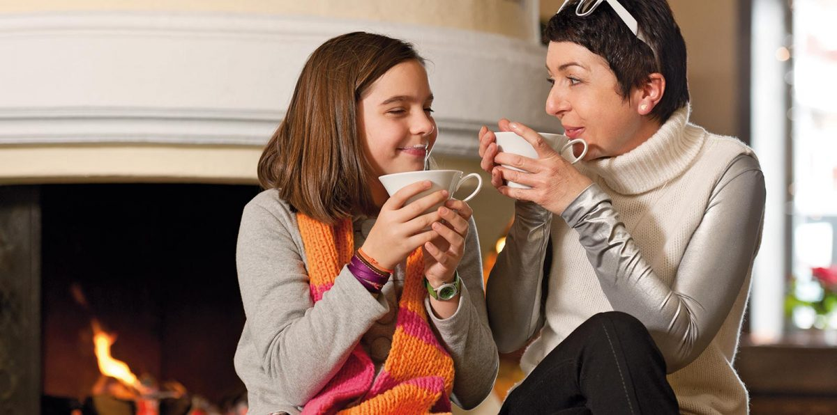 Mother and daughter enjoy hot chocolate in front of the fireplace