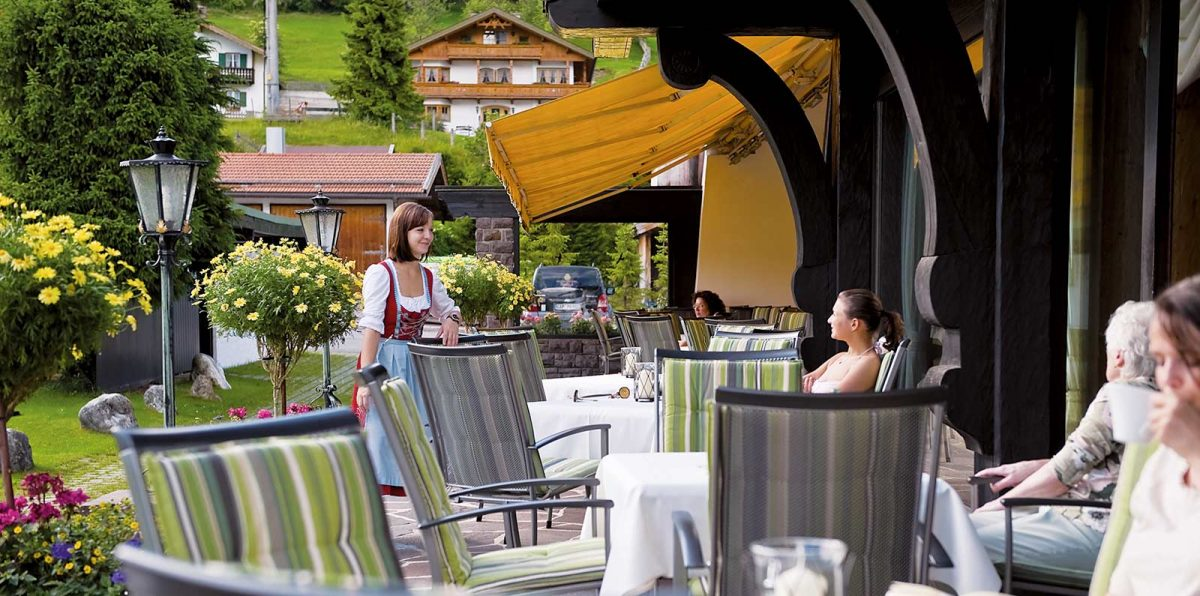 View over the quiet garden terrace. With high-quality seating, flower planting and a friendly waitress in a Dirndl.