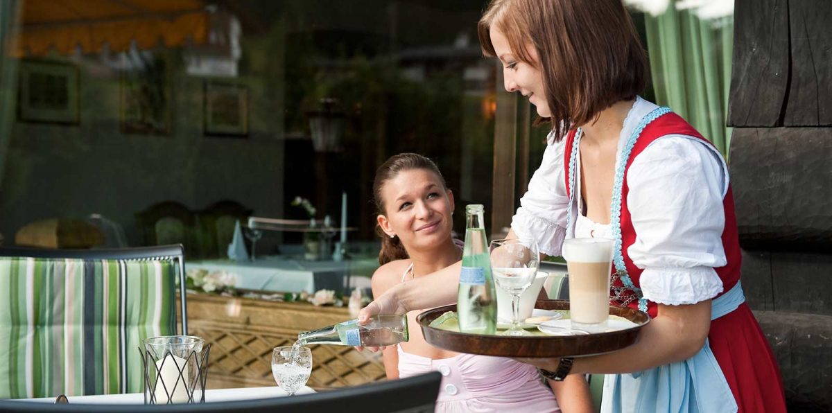 The friendly Dirndl waitress serves latte macchiato and water on the garden terrace.