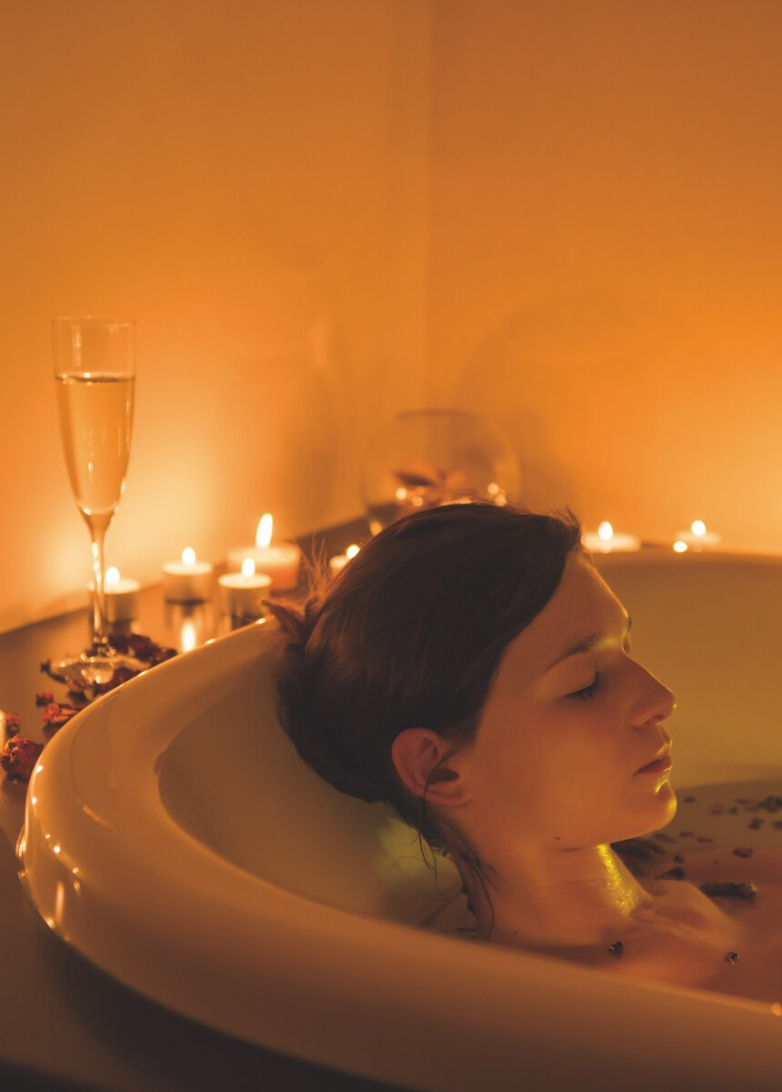 Young woman relaxes with a flower bath in the light and sound tub. Surrounded by candlelight
