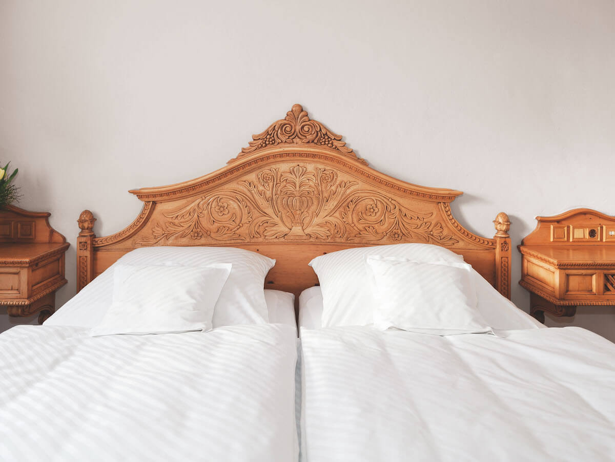 A generous double bed with elaborately carved bed head is found in each of the residence suites