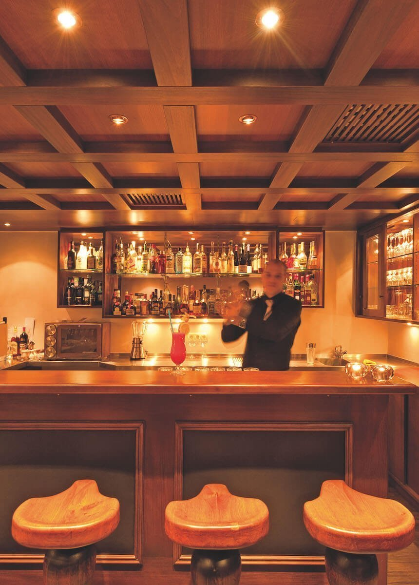 The classical bar with walnut wood paneling radiates cosiness. The barkeeper mixes a cocktail.